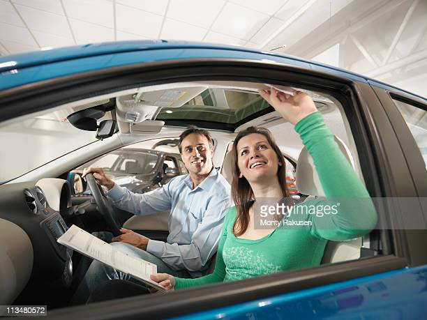 Customers sitting in car look at car interior in car dealership