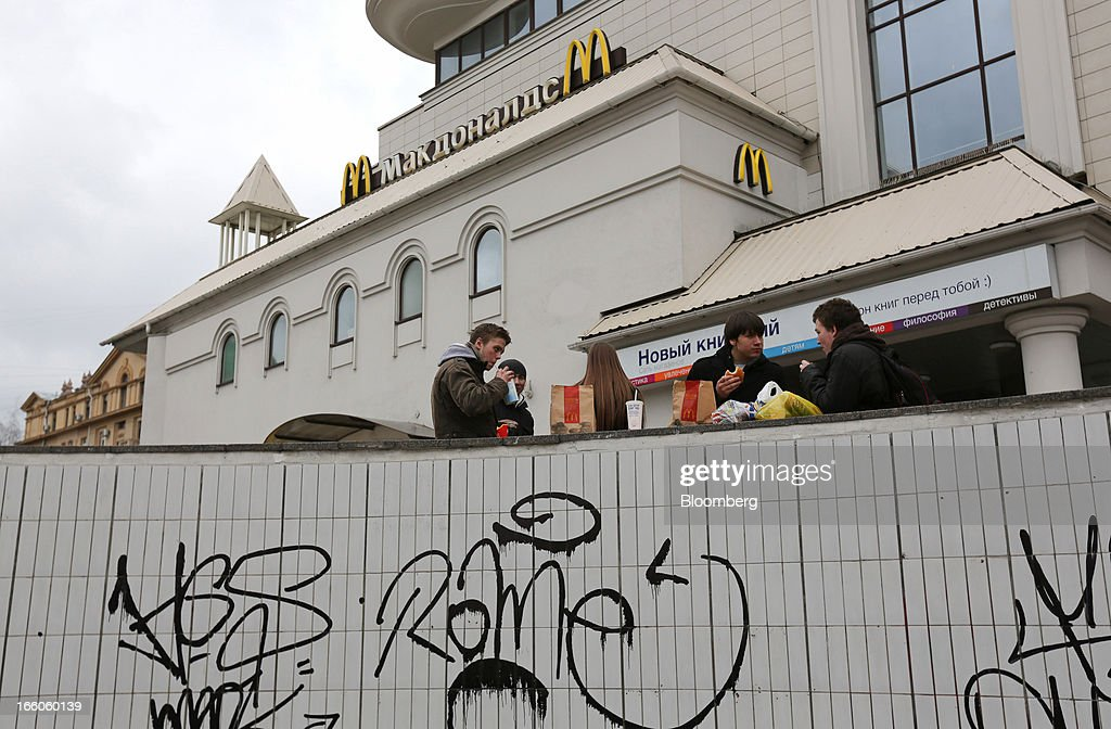 Customers stand and eat meals outside a McDonald's food restaurant in Moscow, Russia, on Sunday, April 7, 2013. McDonald's Corp., which virtually created the market for burgers and fries in the country and convinced Russians it's OK to eat with their hands, must fend off a growing challenge from rivals Burger King Worldwide Inc., Subway Restaurants, Yum! Brands Inc. and Wendy's Co. Photographer: Andrey Rudakov/Bloomberg via Getty Images