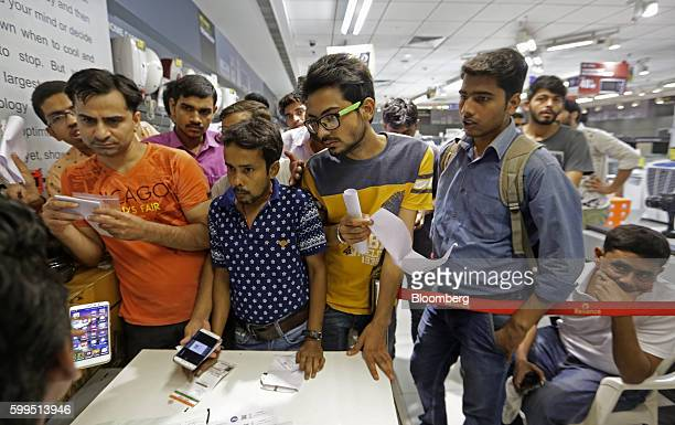 Customers stand at a service desk at a Reliance Digital store a subsidiary of Reliance Industries Ltd in New Delhi India on Monday Sept 5 2016...