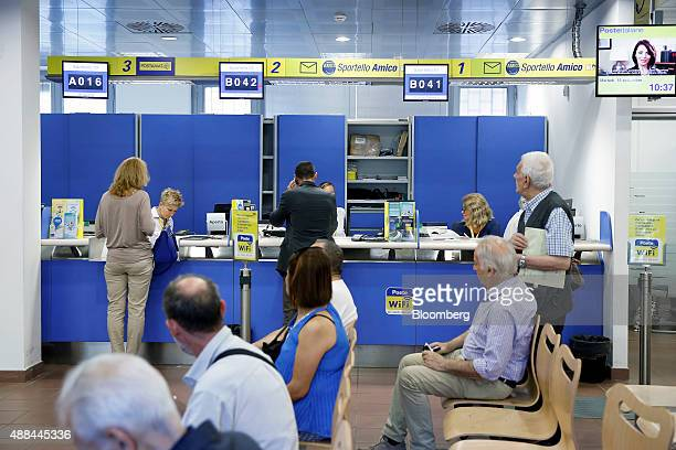Customers stand at booths as they are served by employees inside a Poste Italiane SpA post office in Rome Italy on Tuesday Sept 15 2015 Italy is...