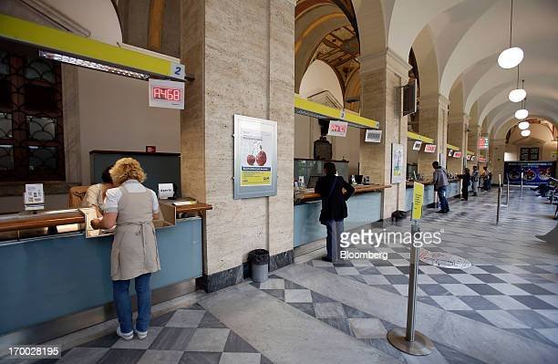 Customers stand at booths as they are served by staff inside a Poste Italiane SpA post office in Rome Italy on Wednesday June 5 2013 Rome based Poste...