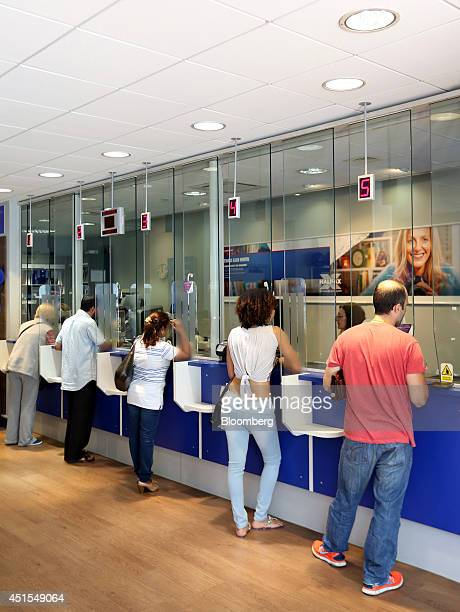 Customers stand at service counters as they are served by staff inside a Halifax bank branch a unit of Lloyds Banking Group Plc in London UK on...