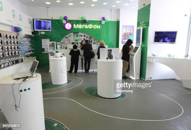 Customers stand at the service counter of a MegaFon PJSC mobile phone store in Moscow Russia on Tuesday Aug 29 2017 MegaFon considers various...