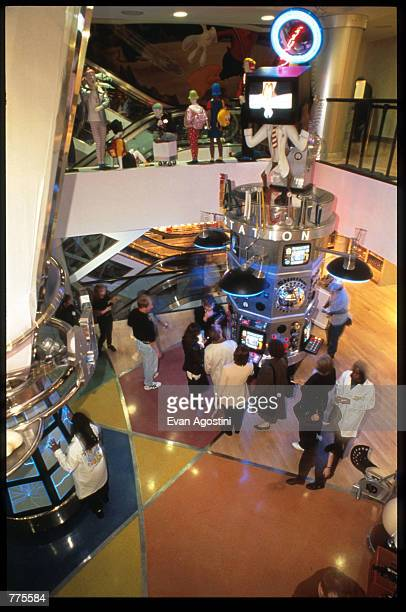 Customers stand in front of an interactive center at the Warner Bros Studio store October 23 1996 in New York City The store originally a three floor...