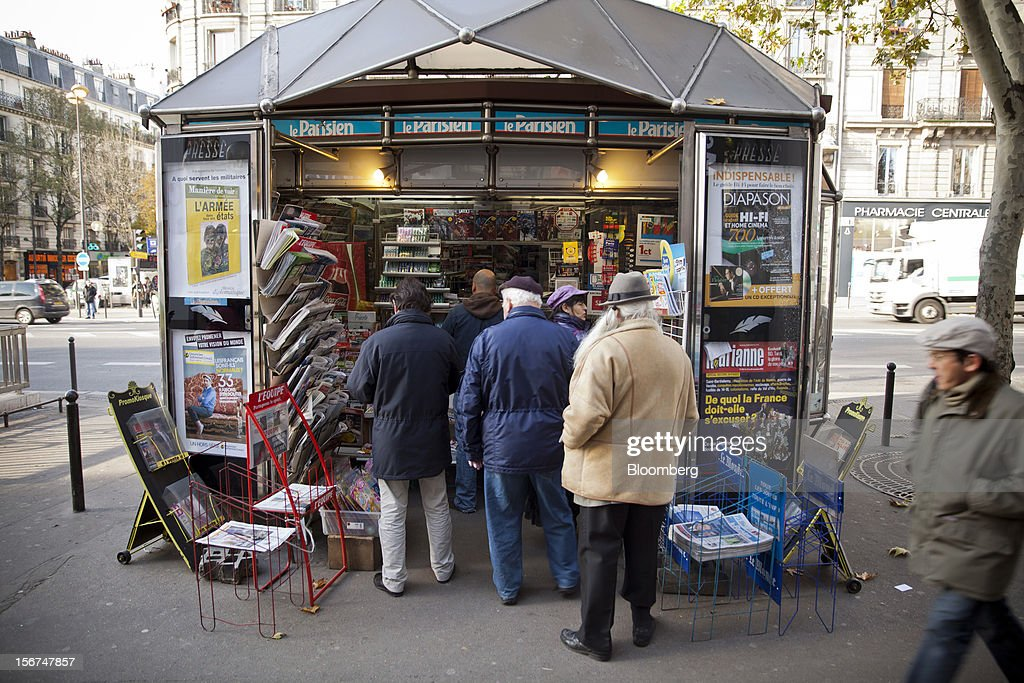 Customers stand in line as they wait to be served outside a news kiosk in Paris, France, on Tuesday, Nov. 20, 2012. France's government bonds fell, with 10-year yields rising the most in a month, after Moody's Investors Service lowered the nation's top credit rating, citing a worsening economic growth outlook. Photographer: Balint Porneczi/Bloomberg via Getty Images