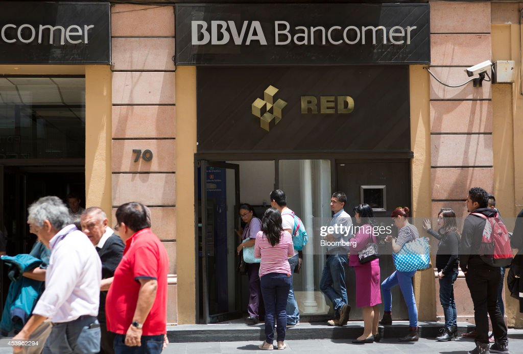 Customers stand in line at a BBVA Bancomer automated teller machine (ATM) in Mexico City, Mexico, on Thursday, Aug. 21, 2014. Mexican consumer prices rose more than analysts expected in the first half of August and the unemployment rate rose to 5.47 percent in July compared with 4.8 percent in June. Photographer: Susana Gonzalez/Bloomberg via Getty Images