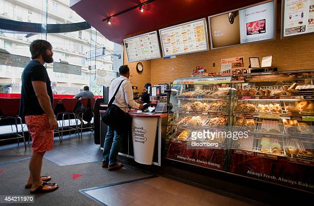 Customers stand in line to order at a Tim Hortons Inc restaurant in downtown Vancouver British Columbia Canada on Tuesday Aug 26 2014 Burger King...