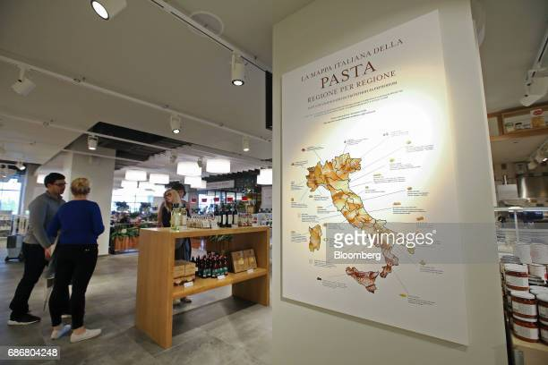 Customers stand near a large wall map showing the regional past of Italy inside the new Eataly food store operated by Eataly Net Srl at the Kievsky...