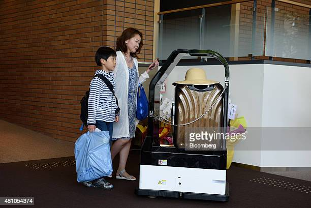 Customers stand next to a Sharp Corp porter robot carrying luggage at the Henn na Hotel operated by Huis Ten Bosch Co a unit of HIS Co in Sasebo...