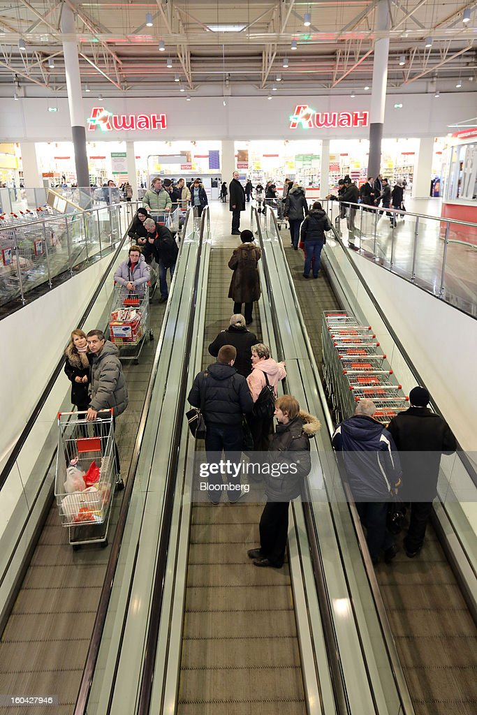 Customers stand on moving walkways outside an Auchan Groupe SA store at the MEGA Belaya Dacha shopping complex, constructed by the real estate development arm of Inter Ikea Systems BV and one of Europe's largest malls, in Moscow, Russia, on Thursday, Jan. 31, 2013. Russian shopping-mall construction may climb to a record this year as retailers take advantage of rising sales by moving into bigger, more modern buildings, Cushman & Wakefield Inc. said. Photographer: Andrey Rudakov/Bloomberg via Getty Images