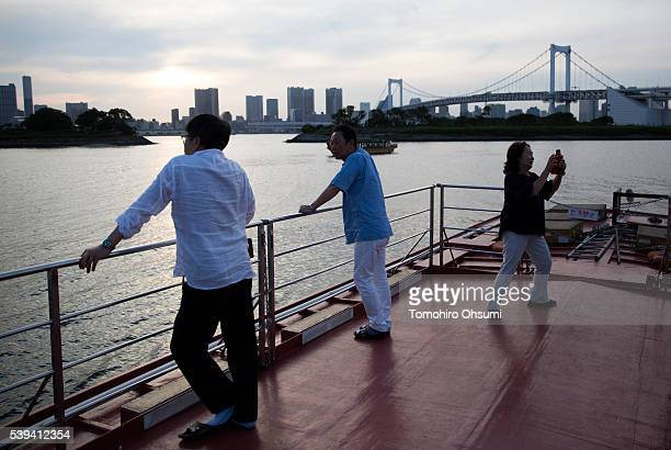 Customers stand on the deck of a yakatabune or traditional low barge style boat operated by Mikawaya shipping agent as it sails through Tokyo Bay on...
