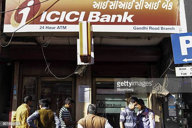 Customers stand outside an ICICI Bank branch in the Gandhi Road area of Ahmadabad Gujarat India on Monday Dec 14 2015 India's rupee is feeling the...