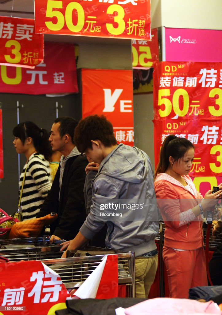 Customers stand surrounded by sale signs as they browse inside a store in Wuhan, China, on Thursday, Oct. 17, 2013. China is scheduled to release third-quarter gross domestic product figures on Oct. 18. Photographer: Tomohiro Ohsumi/Bloomberg via Getty Images