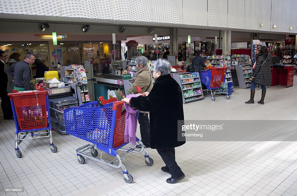 Customers stand with their purchases loaded in shopping carts as they queue at check-out counters inside a Carrefour SA supermarket in Portet sur Garonne, near Toulouse, France, on Tuesday, March 5, 2013. Carrefour's stock has risen 47 percent since Georges Plassat's arrival as chief executive officer, partially offsetting a 71 percent decline in the preceding five years. Photographer: Balint Porneczi/Bloomberg via Getty Images