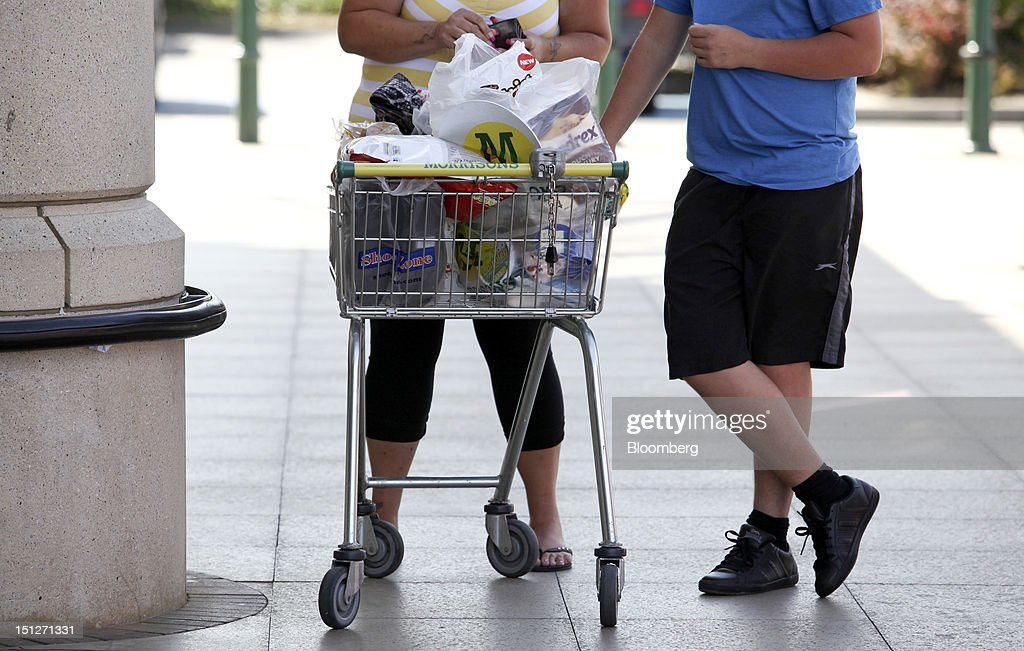 Customers stand with their shopping cart after paying for their goods outside a William Morrison Supermarkets Plc grocery store in Erith, U.K., on Wednesday, Sept. 5, 2012. Morrisons announced that 60 percent of store openings will be in southern England next year as it shifts attention from its northern heritage. Photographer: Chris Ratcliffe/Bloomberg via Getty Images
