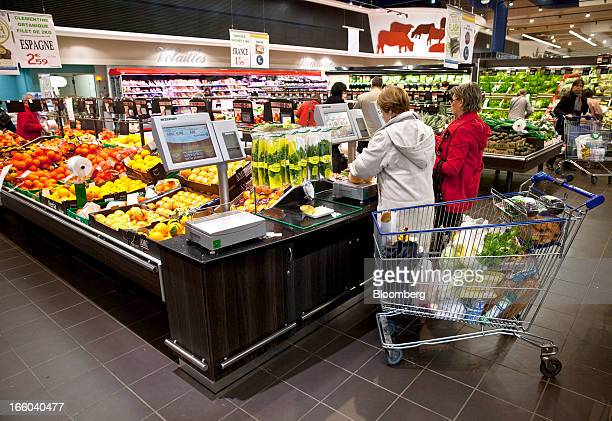 Customers stop to weigh food produce as they shop on the fruit counter inside an E Leclerc hypermarket store in Villefranche de Rouergue France on...