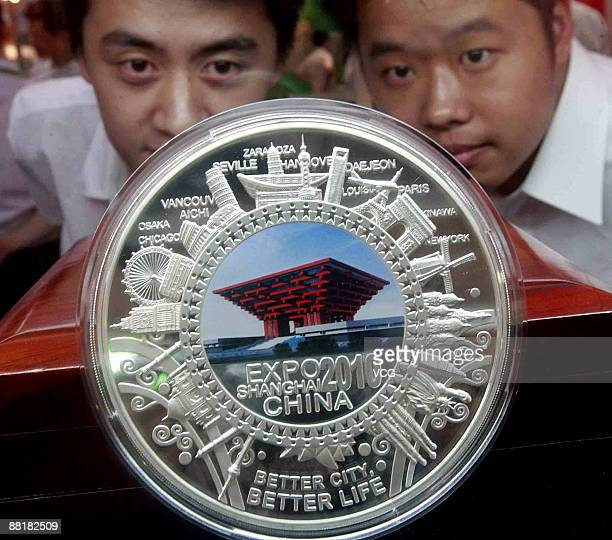 Customers take a close look at Shanghai World Expothemed souvenir silver pan at a fair of licensed products at Shanghai International Exhibition...