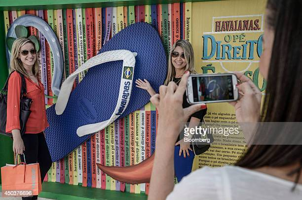 Customers take a picture in front of an over sized flip flop at an Alpargatas SA Havaianas store in Sao Paulo Brazil on Saturday June 7 2014 Sao...