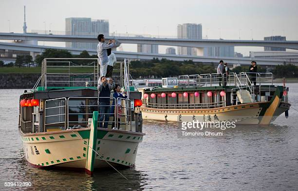 Customers take photographs on the deck of a yakatabune or traditional low barge style boat as it sails through Tokyo Bay on June 11 2016 in Tokyo...