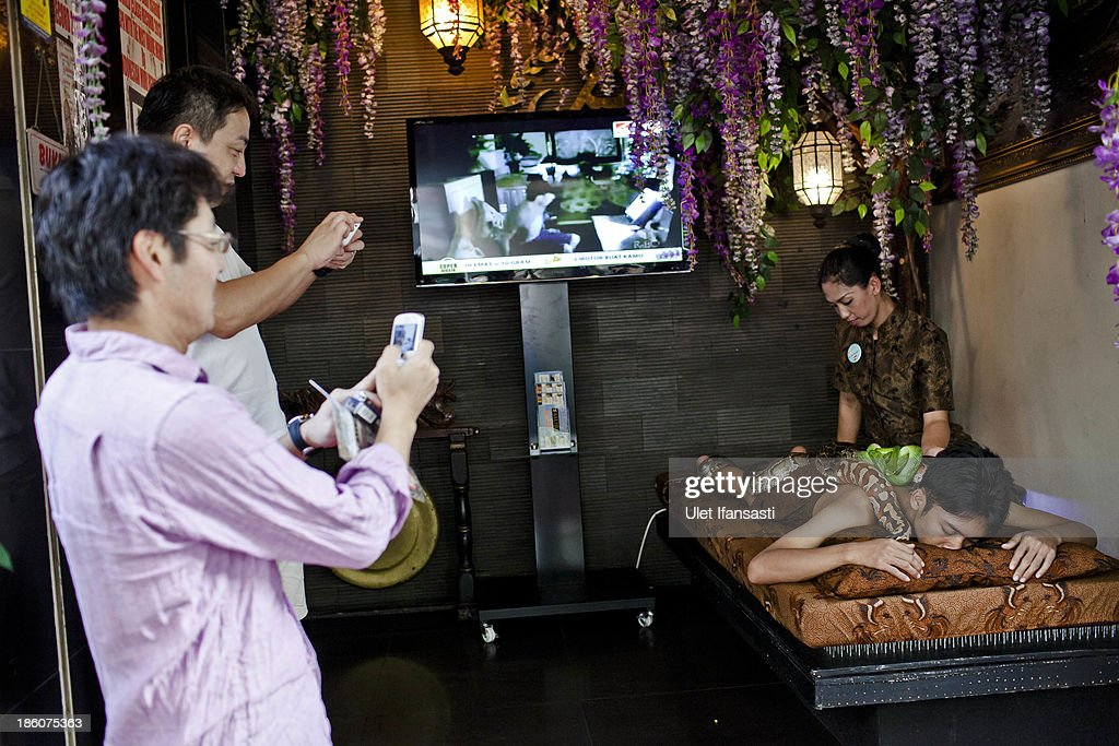 Customers take pictures as staff members perform a massage with pythons at at Bali Heritage Reflexology and Spa on October 27, 2013 in Jakarta, Indonesia. The snake spa offers a unique massage treatment which involves having several pythons placed on the customers body. The movement of the snakes and the adrenaline triggered by fear is said to have a positive impact on the customers metabolism.
