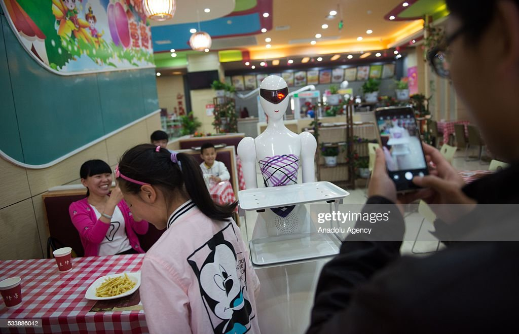 Customers take pictures with the robot waiters at a robot restaurant in Kunshan, China on May 22, 2016. The restaurant has a total of 10 robots in heights of 1.2 meters. Each robot costs 50,000 yuan and all used for delivery and cooking.