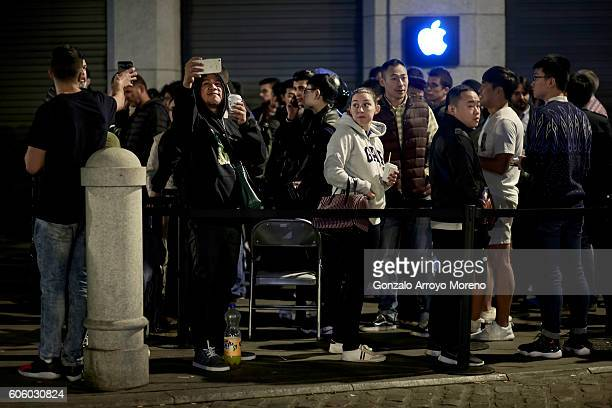 Customers take pictures with their mobile phones as they queue at Puerta del Sol Apple Store before its opening the day the company launches their...