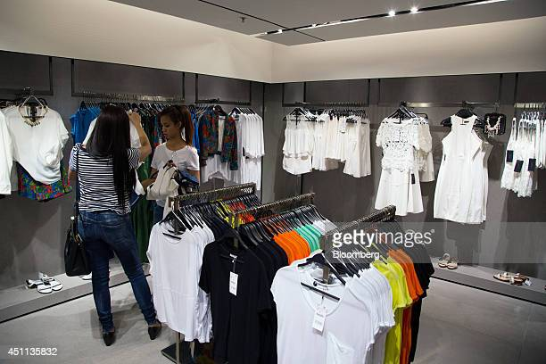 Customers talk as they browse clothes at a Zara store operated by Inditex SA in Hong Kong China on Tuesday June 24 2014 Inditex which has increased...
