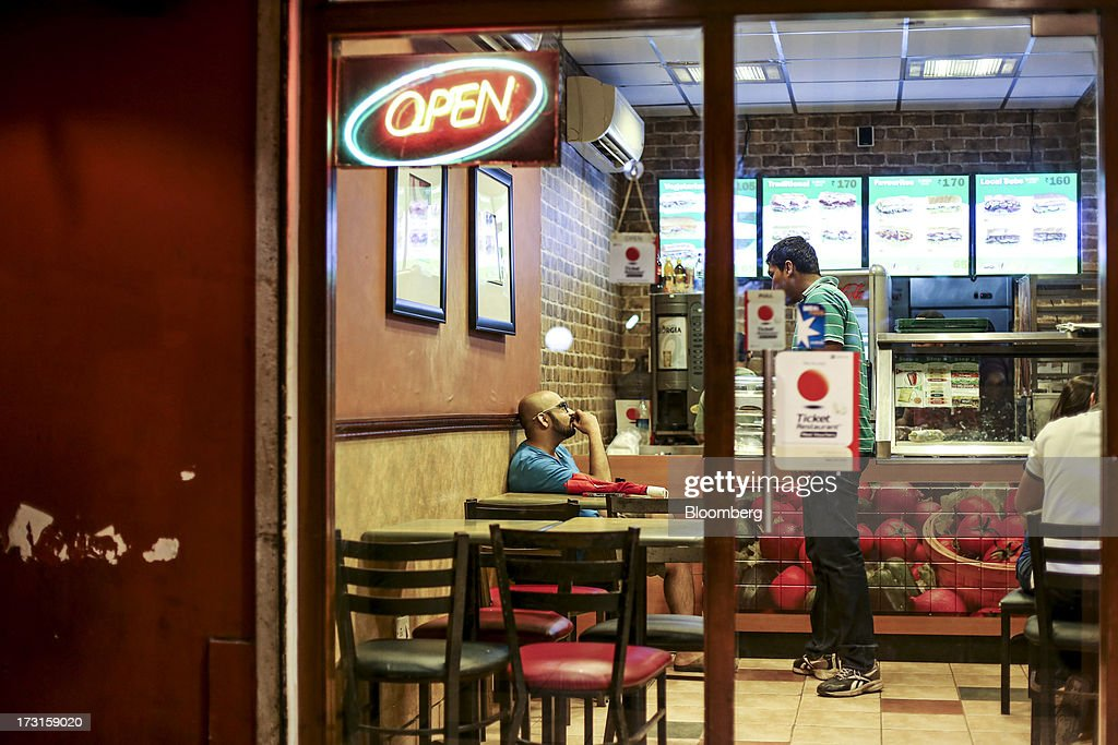 Customers talk inside a Subway fast food restaurant in the suburb of Bandra in Mumbai, India, on Saturday, July 6, 2013. India's consumer price index (CPI) figures for June are scheduled to be released on July 12. Photographer: Dhiraj Singh/Bloomberg via Getty Images