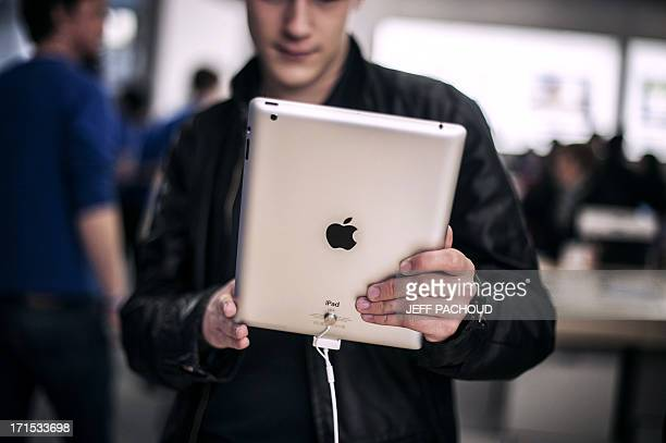 Customers test new IPad on April 4 2012 at the newly Apple store inside the Confluence shopping centre in Lyon on the day of its inauguration AFP...