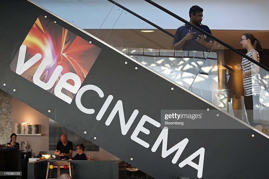 Customers travel on a escalator at a Vue Cinema, operated by Vue Entertainment Ltd., at the Westfield Stratford City retail complex in London, U.K., on Tuesday, June 4, 2013. Vue Entertainment, the U.K. cinema chain bought by private equity firm Doughty Hanson & Co., are continuing to expand in Europe, recently acquiring Poland's second-largest cinema chain Multikino. Photographer: Chris Ratcliffe/Bloomberg via Getty Images