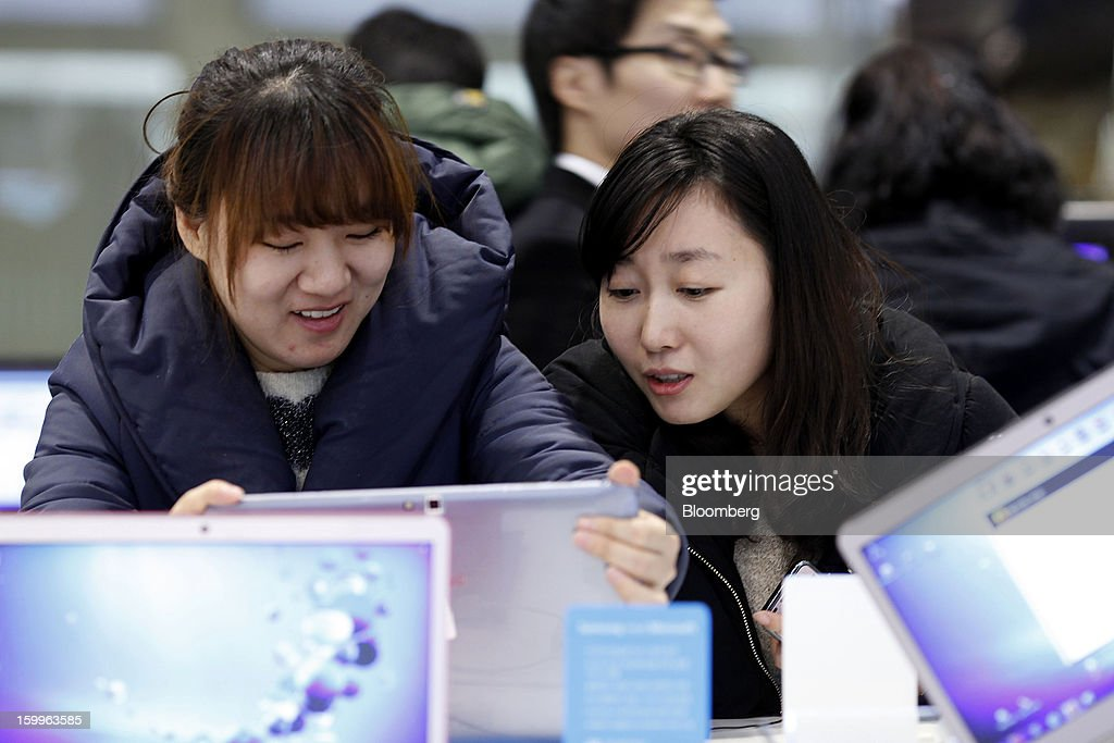 Customers try a Samsung Electronics Co. ATIV Smart PC at the Samsung d'light store in Seoul, South Korea, on Wednesday, Jan. 23, 2013. Samsung, in a preliminary statement of results on Jan. 8, reported an 89 percent jump in profit in the three months ended in December, boosted by its Galaxy line of smartphones. Photographer: Woohae Cho/Bloomberg via Getty Images