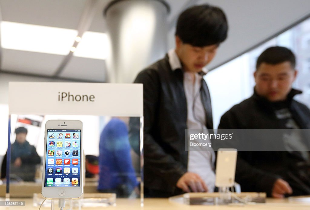 Customers try an Apple Inc. iPad as an iPhone 5 is displayed at the company's store in the Wangfujing area of Beijing, China, on Tuesday, March 12, 2013. Apple's Wangfujing store is the largest in Asia. Photographer: Tomohiro Ohsumi/Bloomberg via Getty Images