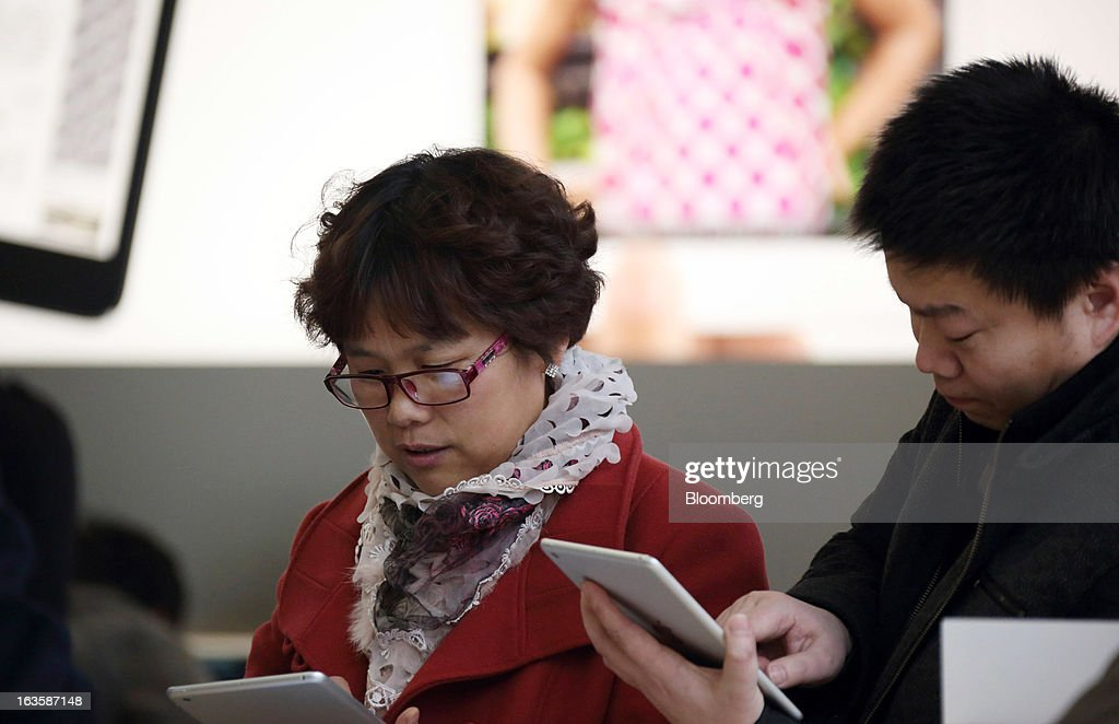 Customers try Apple Inc. iPad Mini's at the company's store in the Wangfujing area of Beijing, China, on Tuesday, March 12, 2013. Apple's Wangfujing store is the largest in Asia. Photographer: Tomohiro Ohsumi/Bloomberg via Getty Images