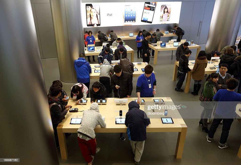 Customers try Apple Inc. products at the company's store in the Wangfujing area of Beijing, China, on Tuesday, March 12, 2013. Apple's Wangfujing store is the largest in Asia. Photographer: Tomohiro Ohsumi/Bloomberg via Getty Images