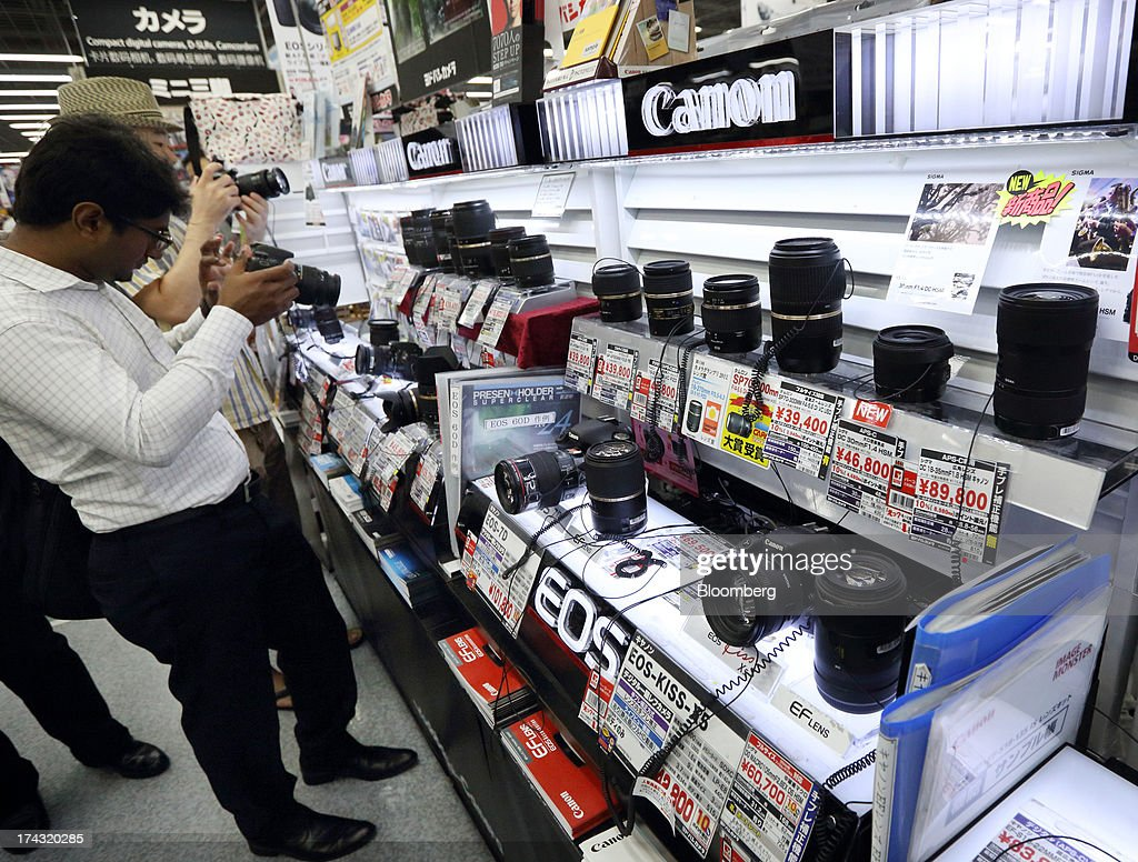Customers try Canon Inc. digital cameras at an electronics store in Tokyo, Japan, on Tuesday, July 23, 2013. Canon Inc., the world's largest camera maker, is scheduled to release earnings on July 24. Photographer: Tomohiro Ohsumi/Bloomberg via Getty Images