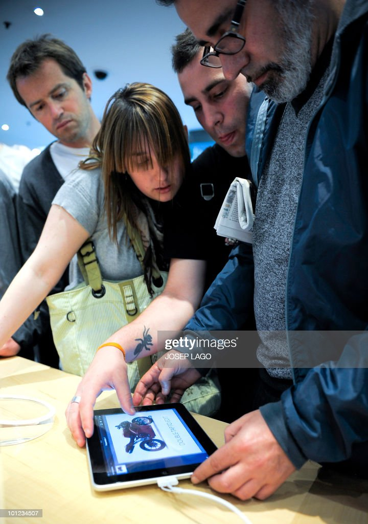 Customers try out Apple's new iPad in a shop in Barcelona on May 28, 2010. Thousands of die-hard Apple fans mobbed shops in parts of Europe and Asia today after the iPad, touted as a revolution in personal computing, began its global launch.