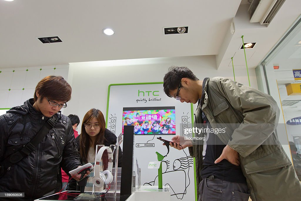 Customers try out HTC Corp. smartphones at one of the company's stores in Taipei, Taiwan, on Sunday, Jan. 6, 2013. HTC is scheduled to release fourth-quarter earnings on Jan. 7. Photographer: Maurice Tsai/Bloomberg via Getty Images