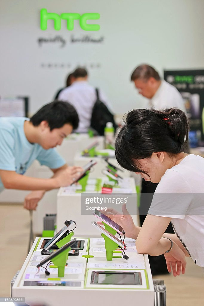 Customers try out HTC Corp. smartphones at one of the company's stores in Taipei, Taiwan, on Thursday, July 4, 2013. HTC is scheduled to announce second quarter earnings on July 8. Photographer: Maurice Tsai/Bloomberg via Getty Images