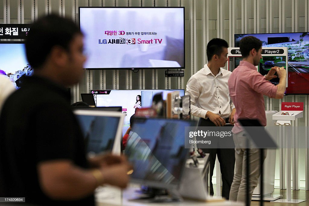 Customers try out LG Electronics Inc. products at one of the company's bestshop stores in the Gangnam area of Seoul, South Korea, on Wednesday, July 24, 2013. LG Electronics, the worlds second-largest television maker, posted second-quarter profit that missed analyst estimates on slowing demand for sets and increased spending on marketing for smartphones. Photographer: Woohae Cho/Bloomberg via Getty Images