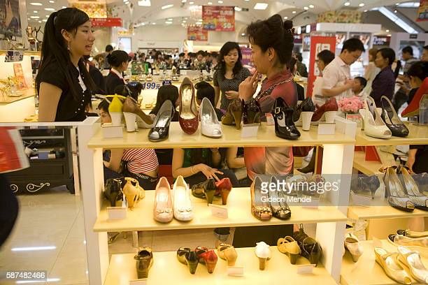 Customers try out new shoes as shopping fever hits the Grand Pacific Mall in the Xidan shopping area during the May holiday break