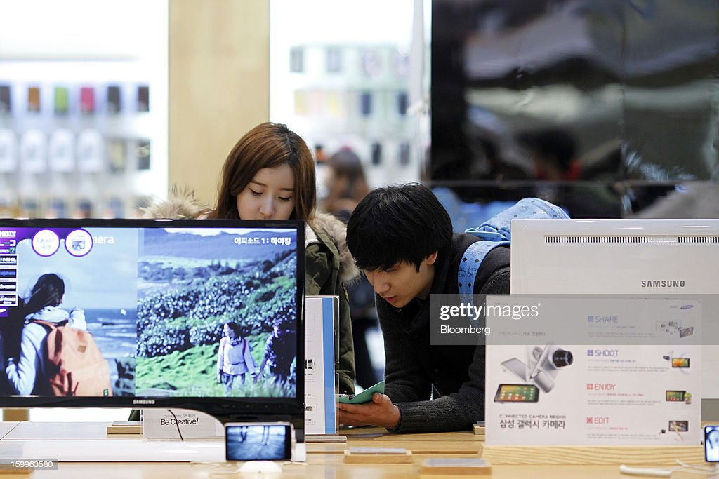 Customers try Samsung Electronics Co. products at the Samsung d'light store in Seoul, South Korea, on Wednesday, Jan. 23, 2013. Samsung, in a preliminary statement of results on Jan. 8, reported an 89 percent jump in profit in the three months ended in December, boosted by its Galaxy line of smartphones. Photographer: Woohae Cho/Bloomberg via Getty Images
