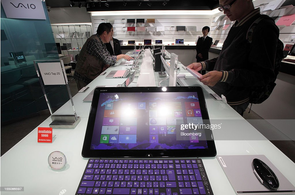 Customers try Sony Corp. laptop computers at the company's showroom in Tokyo, Japan, on Thursday, Nov. 1, 2012. Sony, Japan's biggest consumer-electronics exporter, unexpectedly posted its seventh straight quarterly loss on falling demand for its TVs as consumers flock to Apple Inc. and Samsung Electronics Co. devices. Photographer: Tomohiro Ohsumi/Bloomberg via Getty Images