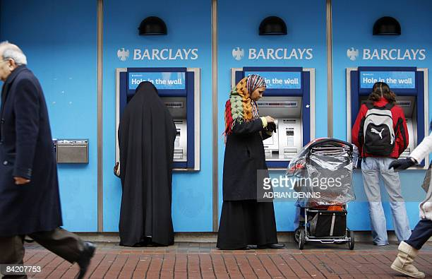 Customers use a cashpoint machine at a Barclays Bank branch in Hounslow west London on January 8 2009 The Bank of England on Thursday cut its key...
