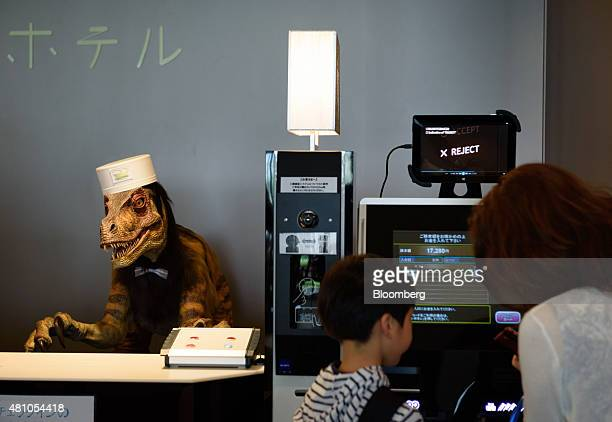 Customers use a checkin machine as a Kokoro Company Ltd humanoid robot stands at the reception desk of Henn na Hotel operated by Huis Ten Bosch Co a...