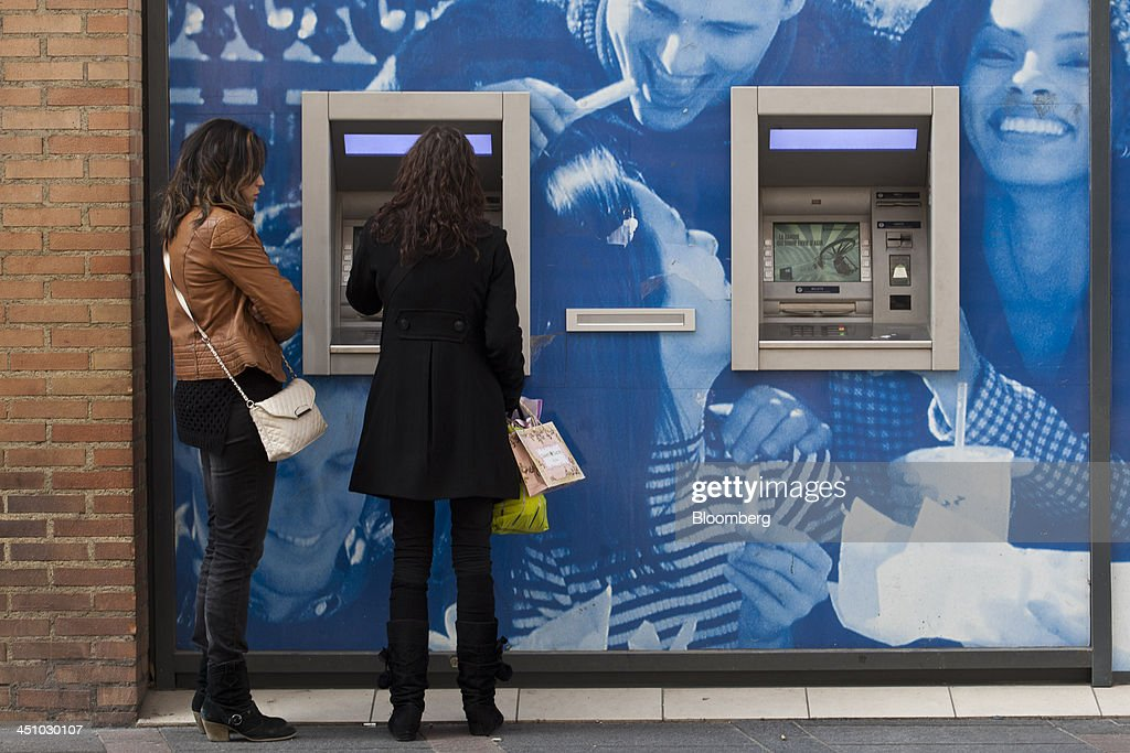 Customers use an automated teller machine (ATM) outside a branch of Banque Populaire in Toulouse, France, on Wednesday, Nov. 20, 2013. France's gross domestic product fell 0.1 percent in the three months through September, national statistics office Insee said in an e-mailed statement. Photographer: Balint Porneczi/Bloomberg via Getty Images