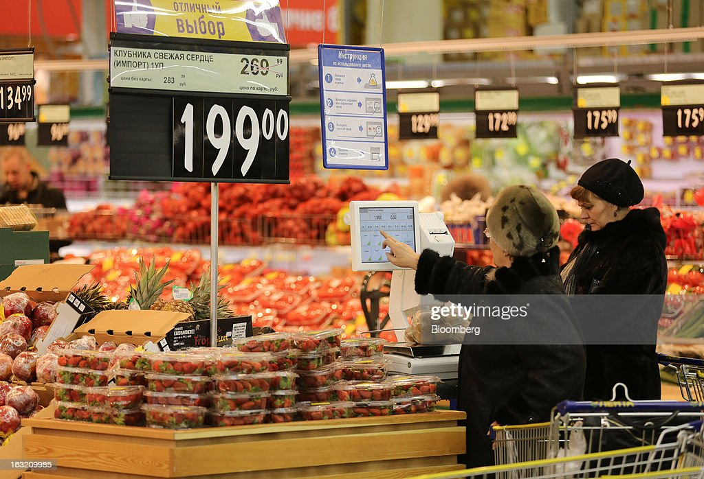 Customers use an electronic scale to check the price of their fresh fruit and vegetables inside a Lenta LLC supermarket in Prokopyevsk, Kemerevo region, Russia, on Wednesday, March 6, 2013. Lenta LLC, a Russian hypermarket operator controlled by TPG Capital, is selling its first bond to expand after using company funds for a leveraged buyout by the U.S. firm. Photographer: Andrey Rudakov/Bloomberg via Getty Images
