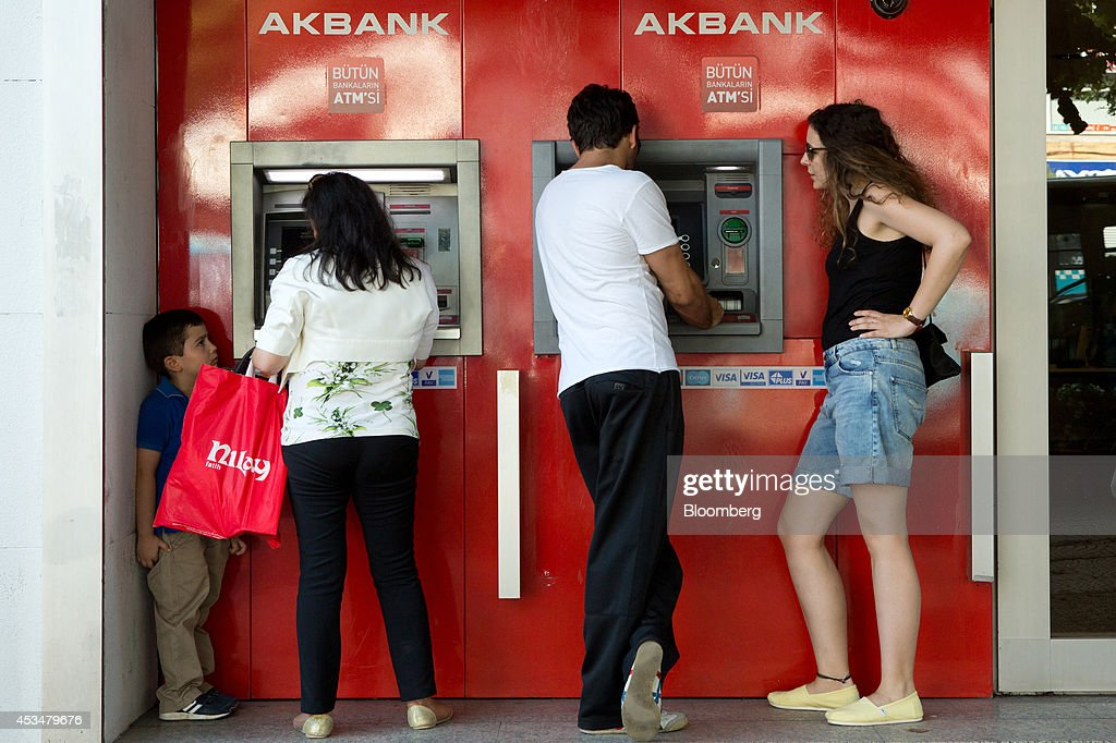 Customers use automated teller machines (ATM) operated by Akbank TAS bank in the Besiktas district of Istanbul, Turkey, on Sunday, Aug. 10, 2014. Investors said they will need to assess the next government's commitment to financial stability should Turkish Prime Minister Recep Tayyip Erdogan assume the presidency this month. Photographer: Kerem Uzel/Bloomberg via Getty Images