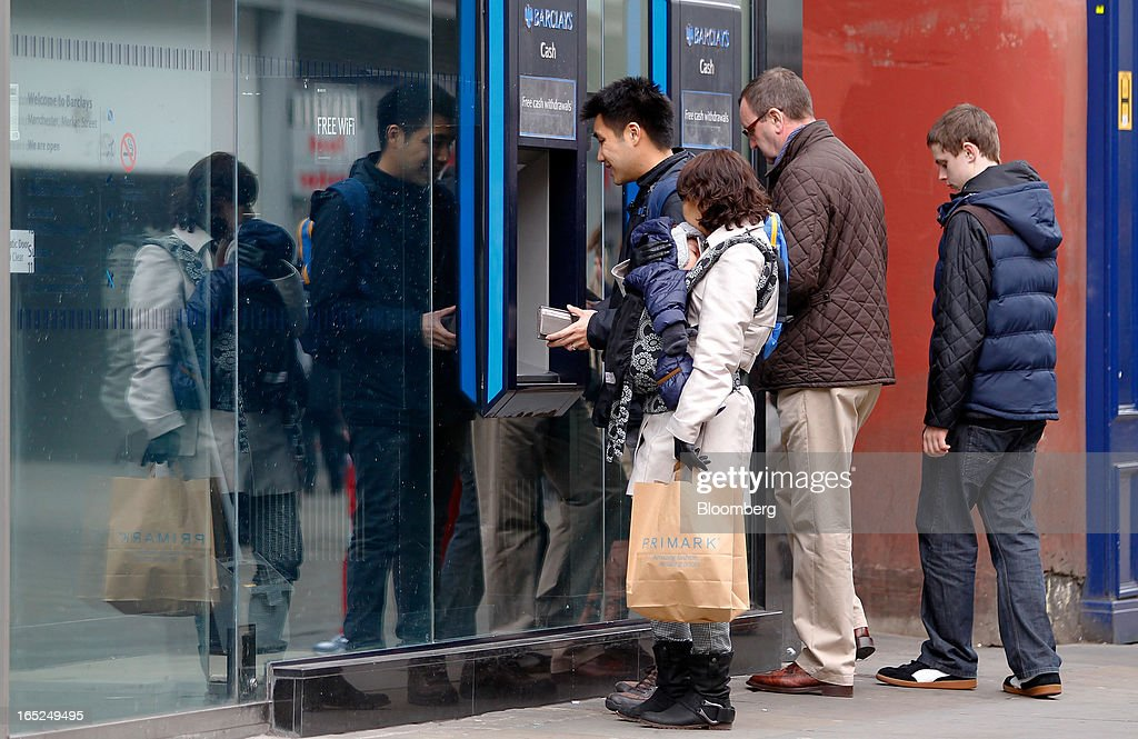 Customers use automated teller machines (ATM) operated by Barclays Plc in central Manchester, U.K., on Monday, April 1, 2013. U.K. retail sales unexpectedly stagnated in March in a sign that consumer spending remains under pressure from higher energy bills and weak wage growth. Photographer: Paul Thomas/Bloomberg via Getty Images
