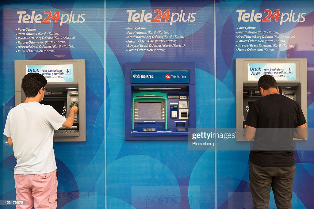 Customers use automated teller machines (ATM) operated by Yapi Kredi AS bank in the Besiktas district of Istanbul, Turkey, on Sunday, Aug. 10, 2014. Investors said they will need to assess the next government's commitment to financial stability should Turkish Prime Minister Recep Tayyip Erdogan assume the presidency this month. Photographer: Kerem Uzel/Bloomberg via Getty Images