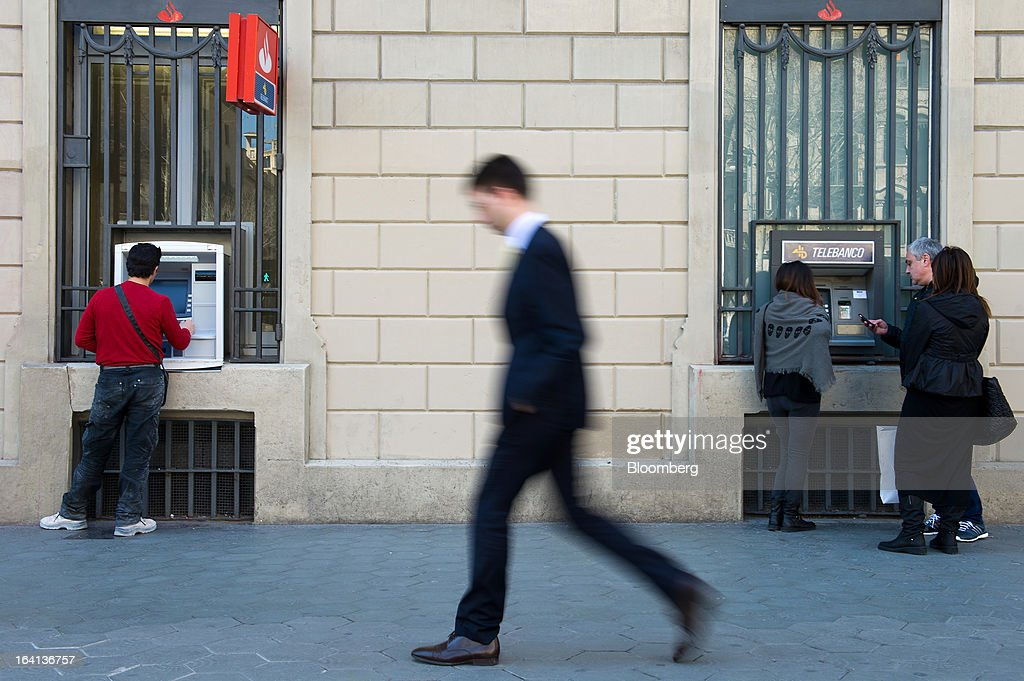 Customers use automated teller machines (ATM) outside a Banco Santander SA branch in Barcelona, Spain, on Wednesday, March 20, 2013. Officials from the troika of international creditors -- the ECB, the International Monetary Fund and the European Commission -- are in Cyprus discussing further capital controls and possibly extending a bank holiday to the end of the week, a European official familiar with the talks said on condition of anonymity because the discussions are confidential. Photographer: David Ramos/Bloomberg via Getty Images